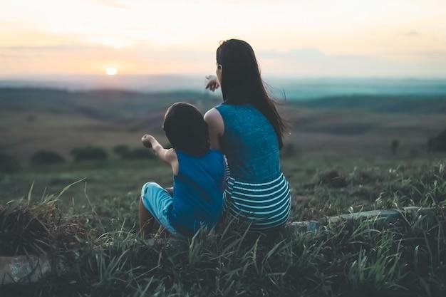 Mère et fils en regardant le coucher de soleil à l'horizon