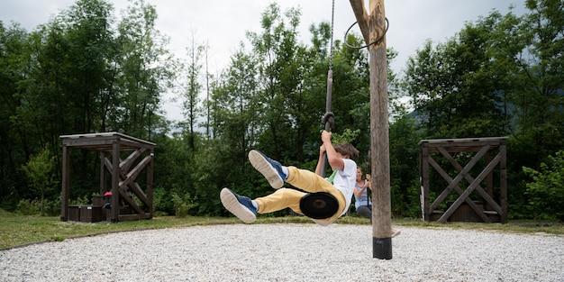 Mère et fils s'amusant sur une aire de jeux chevauchant un carrousel spécial comme une balançoire à l'extérieur dans un parc.