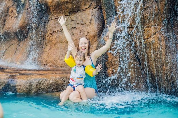Mère et fils se détendre sous une cascade dans un parc aquatique