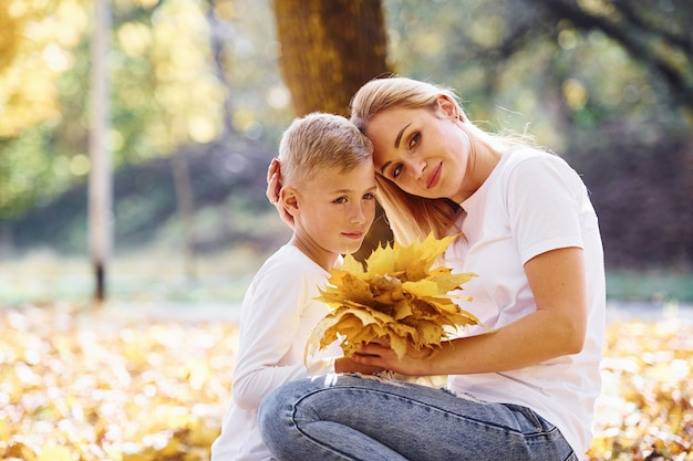 Mère avec fils se reposer dans un magnifique parc d'automne aux beaux jours.