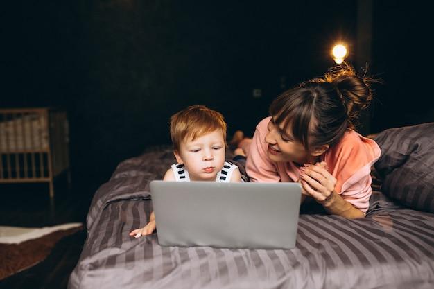 Mère avec fils travaillant sur l'ordinateur au lit