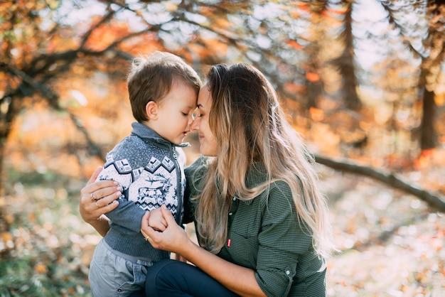 Mère avec fils trois ans en automne la forêt, étreinte et tendresse