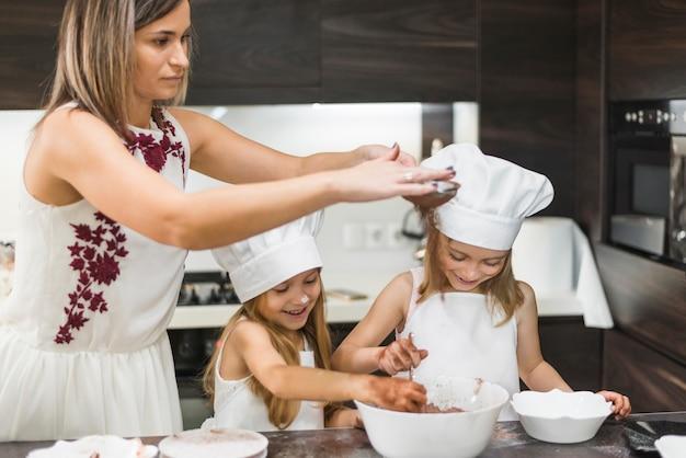 Mère filtrant la poudre de cacao à travers une passoire pendant que sa fille se mélange dans un bol