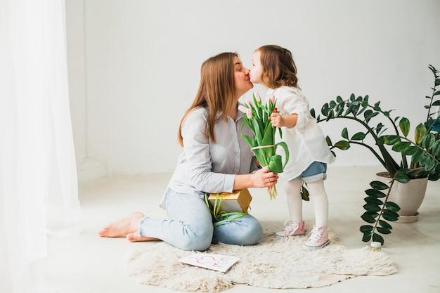 Mère avec des fleurs et sa fille s'embrasser