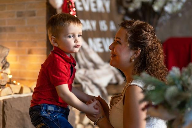 Mère et garçon sous l'arbre de noël avec des cadeaux. femme avec enfant pour le nouvel an