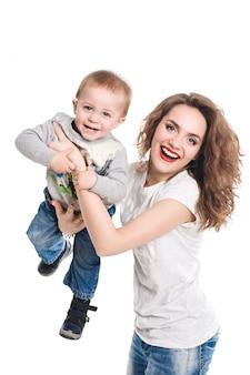 La mère garde son fils dans ses bras, pointant la caméra