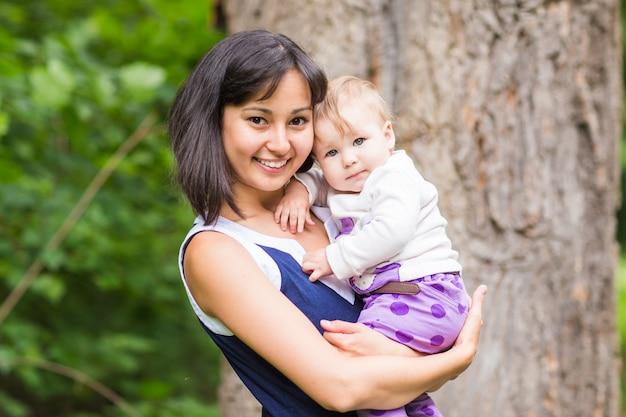 Mère heureuse de race mixte avec portrait de bébé fille en plein air.