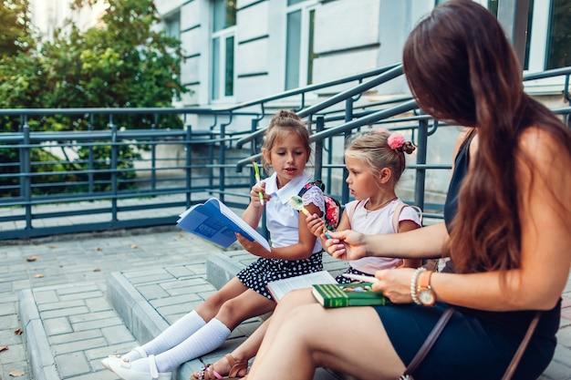 Une mère heureuse et ses filles passent du temps ensemble après les cours. enfants lisant des livres à faire leurs devoirs à l'extérieur de l'école primaire.