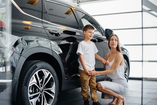 Une mère heureuse avec son jeune fils choisit une nouvelle voiture chez un concessionnaire automobile. acheter une voiture.