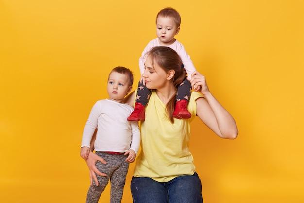Une mère heureuse tient un enfant sur son cou et un autre câlin