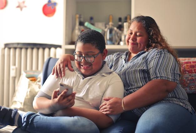 Mère hispanique et son fils travaillant avec un smartphone assis sur le canapé