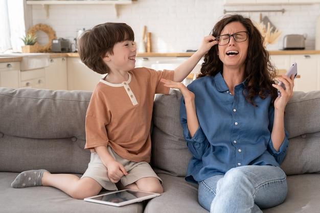 Mère impuissante frustrée pleurant d'anxiété avec un petit fils hyperactif assis ensemble sur un canapé