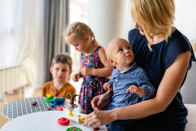 La mère ou l'institutrice enseigne à ses enfants à travailler avec des jouets en argile colorés. concept de créativité pour enfants