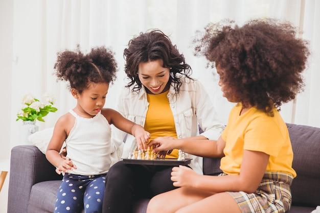 Mère intelligente de bons soins, apprenant à ses enfants à être des génies et des petites filles intelligentes apprenant à jouer aux échecs en vacances à la maison.