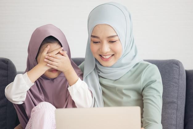 Une mère islamique élève sa fille de près pour un appel vidéo en ligne