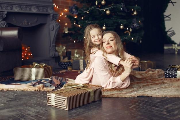 Mère avec jolie fille à la maison près de cheminée