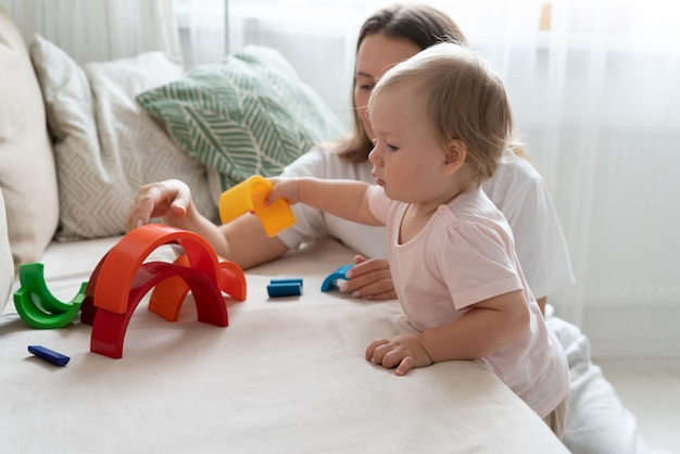 Mère jouant des jouets en plastique avec un enfant sur un canapé développement de bébé et activité de loisirs à la maison