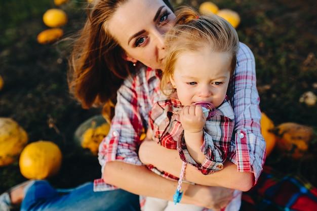 Mère jouant avec sa fille sur un champ avec des citrouilles
