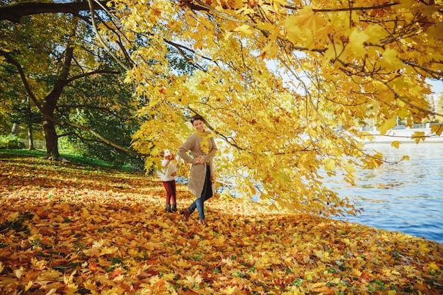 Mère jouant avec sa fille dans le parc. maman et son enfant jouent ensemble en automne à l'extérieur. heureux famille aimante s'amuser. élégant mère et enfant portent.