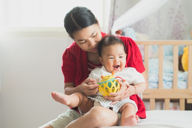 Mère jouant avec son bébé au lit