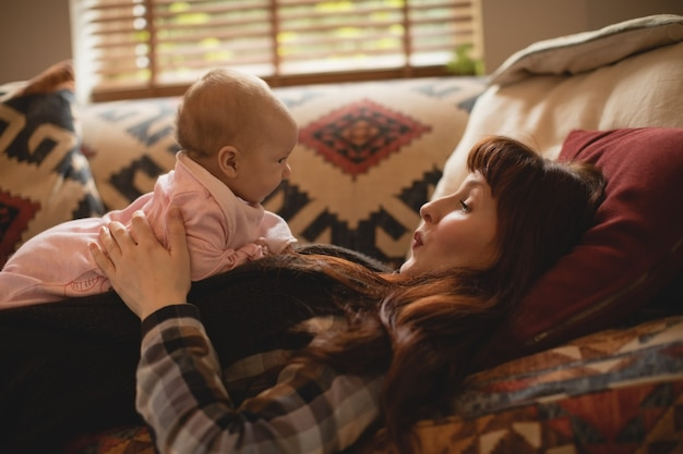Mère jouant avec son bébé sur le canapé