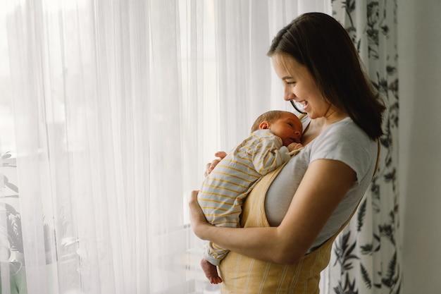 Mère jouant avec son nouveau-né à la maison près de la fenêtre. bébé et maman heureux.