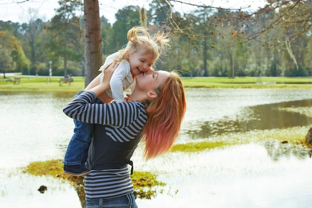 Mère jouant vomir bébé fille dans un lac