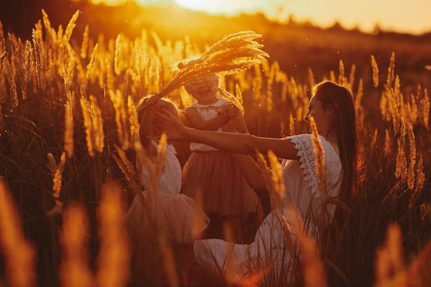 Mère joue avec sa fille dans le parc au coucher du soleil. famille heureuse, maman et deux filles.