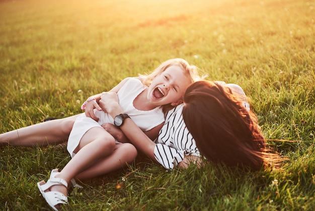 Mère joue avec sa fille dans la rue dans le parc au coucher du soleil
