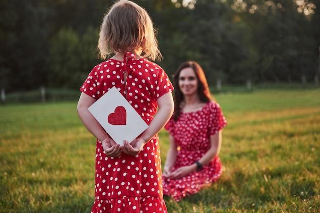 Mère joue avec sa fille dans la rue dans le parc au coucher du soleil.