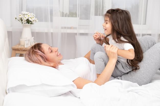 Mère joue avec sa petite fille active au lit à la maison, s'amuse, activité avec les enfants.