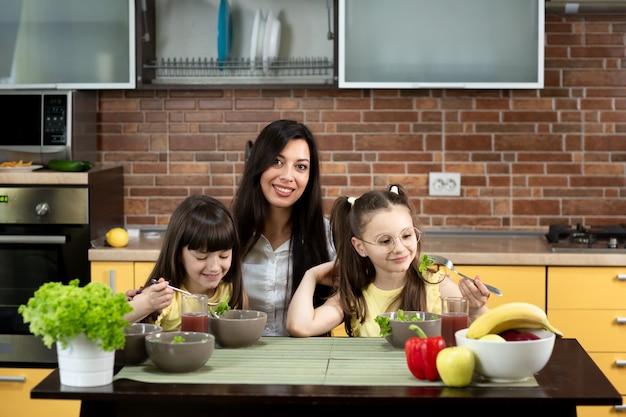 Une mère joyeuse et deux filles mangent ensemble une salade saine à la maison. le concept de saine alimentation, les valeurs familiales, le temps passé ensemble