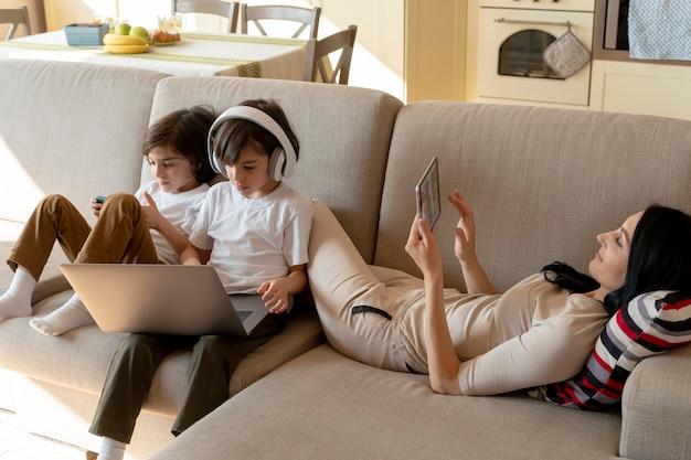 Mère et jumeaux utilisant différents appareils à la maison