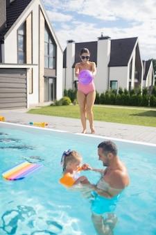 Mère lançant la balle. mère portant des lunettes de soleil lançant une balle tandis que mari et fille nageant dans la piscine