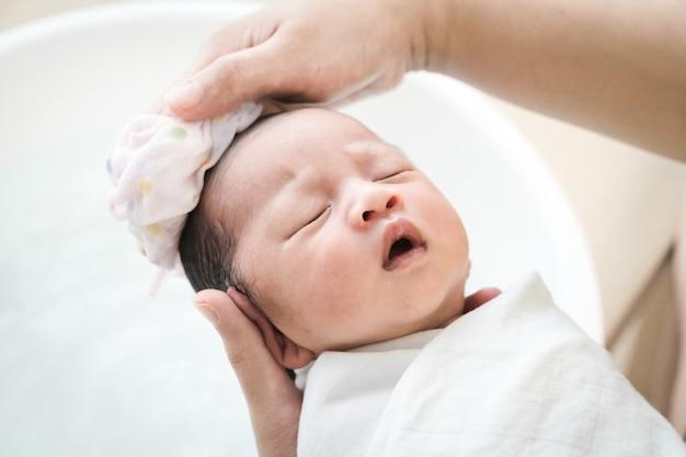 La mère lave les cheveux de bébé. maman nettoie ses cheveux de bébé.