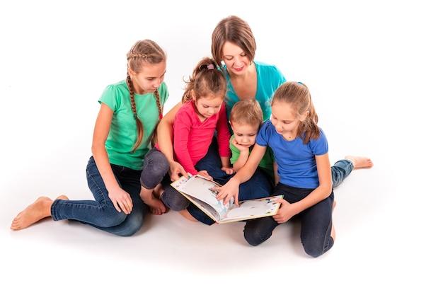 Mère lisant un livre aux enfants isolés sur blanc. travail d'équipe, concept de créativité.