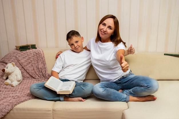 Mère lisant avec son fils sur le canapé. ils montrent les pouces vers le haut