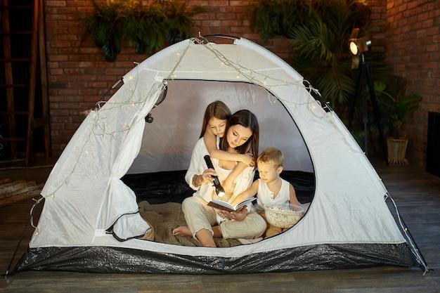 Mère lit un livre de contes de fées pour ses enfants assis dans une tente la nuit. maman fils et fille lisant un livre avec une lampe de poche dans leurs mains