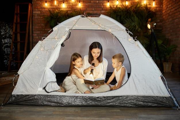 Mère lit un livre de contes de fées pour ses enfants assis dans une tente la nuit