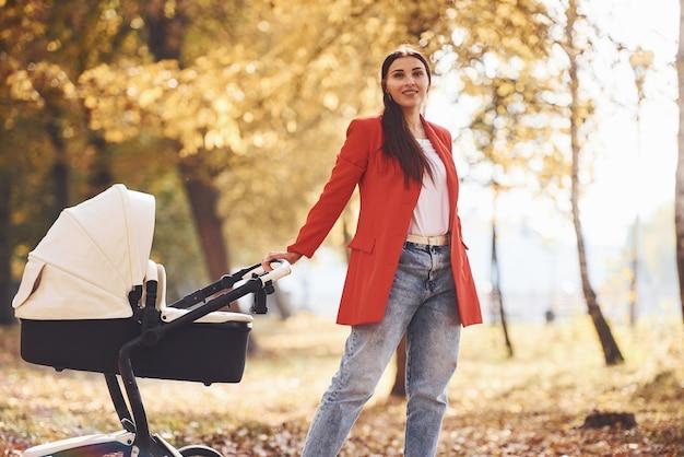 Une mère en manteau rouge se promène avec son enfant dans le landau dans le parc avec de beaux arbres à l'automne.