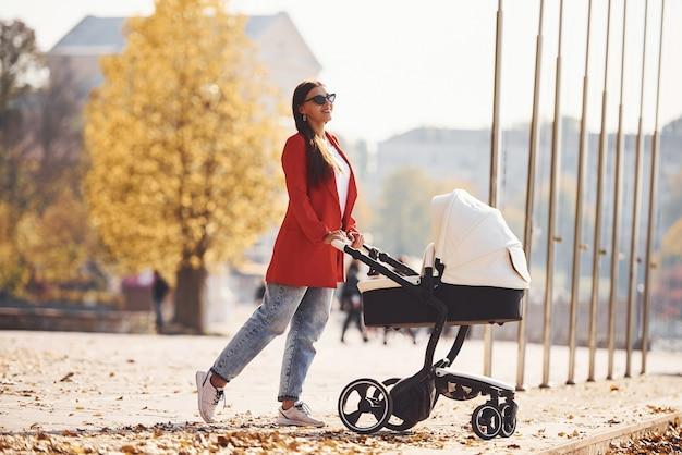 Une mère en manteau rouge se promène avec son enfant dans le landau du parc à l'automne.