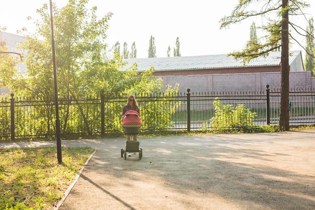 Mère marchant en poussant une poussette dans le parc.