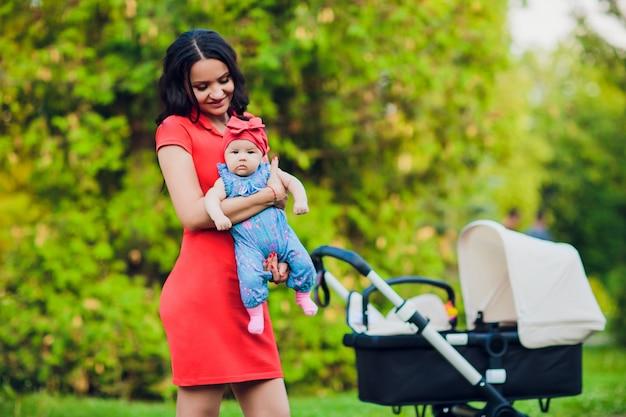 Mère marche avec poussette landau bébé, transport en ville. concept d'amour et de famille.