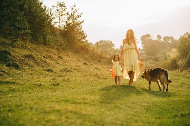 Mère marcher avec sa petite fille et leur chien