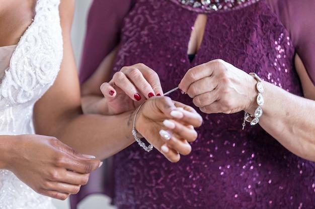 La mère de la mariée l'aide à porter des bijoux de mariage