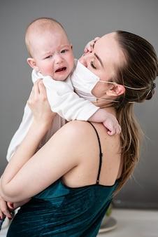 Mère en masque de protection médicale tient son bébé dans ses bras pendant la pandémie de coronovirus et covid-19