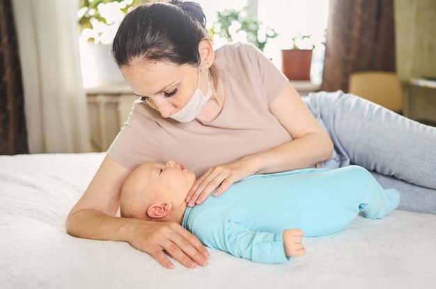 Mère en masque de protection tenant son fils nouveau-né