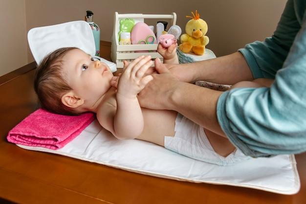 Mère massant le corps d'un adorable bébé allongé après le changement de couche