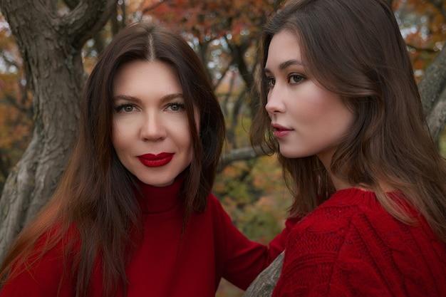 Mère mature étreignant avec sa fille adolescente en plein air dans la nature le jour de l'automne. mode d'automne, pulls rouges chauds. marcher dans la forêt d'automne