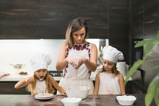Une mère mélange de la poudre de cacao pour faire des biscuits avec ses filles dans la cuisine